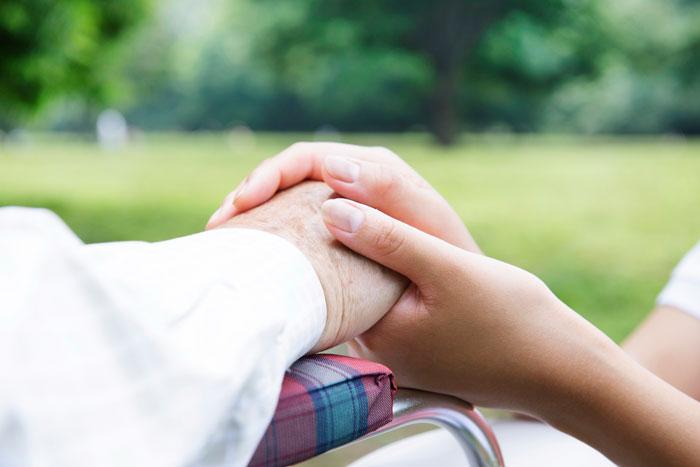高齢者の手を握る女性